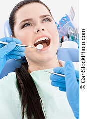 Dentist examines the mouth of the patient on the dentist's...