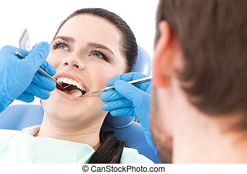 Dentist examines the oral cavity of a pretty patient on the ...