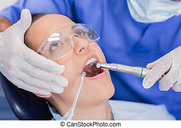 Dentist examining a patient with tools