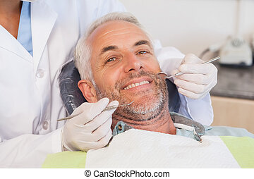 Dentist examining a patients teeth in the dentists chair at ...
