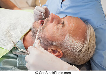 Dentist examining a patients teeth in the dentists chair at...