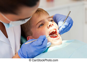 dentist examining boys teeth