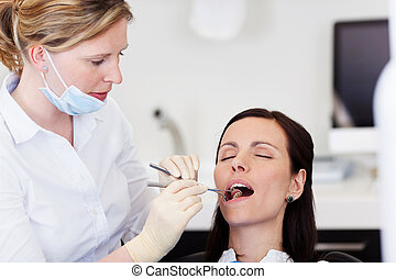 Dentist Examining Female Patients Mouth In Clinic - Female...