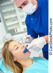 dentist examining his female patients mouth
