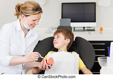 Dentist Explaining Brushing Procedure To Little Boy In Clinic