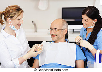 Dentist Explaining Teeth Model To Male Patient