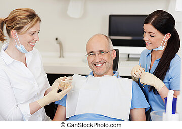 Dentist explaining teeth model to smiling male patient at clinic