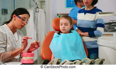 Dentist explaining to girl procedure of extraction using model of dental teeth
