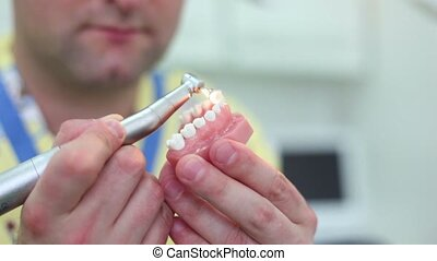 Dentist grinds teeth of jaw in his hand at dental surgery,...