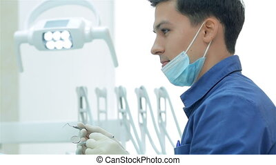Dentist holding a dental instrument in his hands