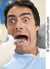dentist holding a syringe and anesthetizing his terrified...