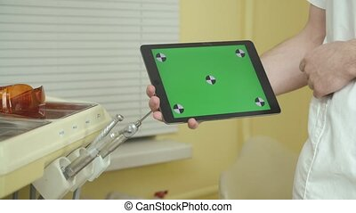 Dentist holds a tablet with a green screen for your content