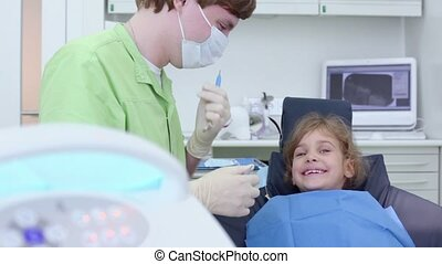 Dentist holds dental tool and speak with girl sits in chair