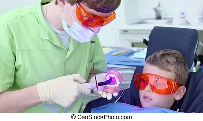 Dentist holds jaw and uses light for harden filling near boy