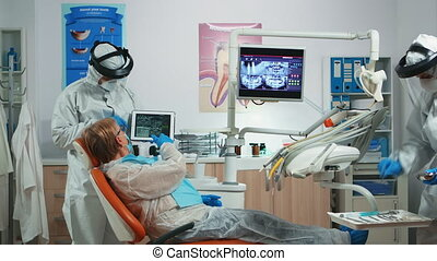 Dentist in coverall examining x-ray image on tablet