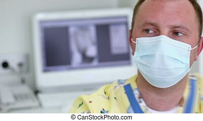 Dentist in medical mask moves light in dental surgery