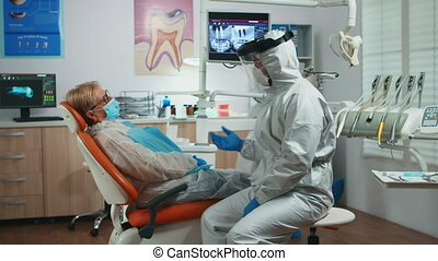 Dentist doctor in protection suit explaining to senior patient the dental surgery process during covid-19 pandemic. Nurse and orthodontist wearing face shield coverall, mask gloves before examination