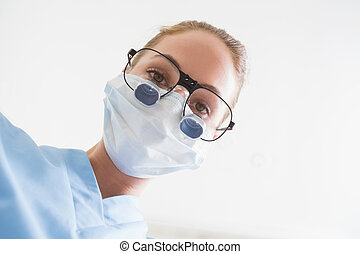 Dentist in surgical mask and dental loupes looking down over...