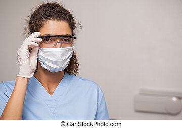 Dentist in surgical mask and protective glasses