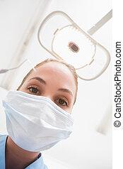 Dentist in surgical mask holding dental explorer over patient