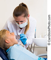 Dentist in white is taking examination of a young boy in clinic.