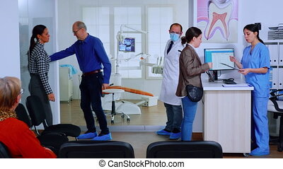 Dentist inviting senior woman in consultation dental room while nurse giving to patients forms to fill indicating to sit on chair in waiting area. Concept of crowded professional orthodontist office.
