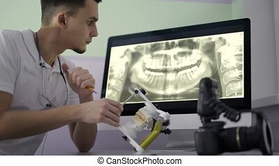 Dentist is examining gypsym teeth model in his cabinet