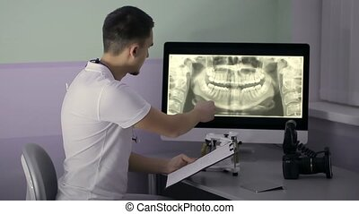 Dentist is examining results of orthopantomogram in his cabinet