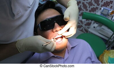 Dentist is healing client teeth with mouth mirror.