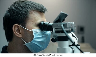 Dentist Is Looking Through Dental Microscope With Camera....