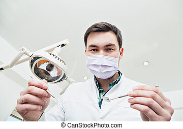Dentist leaned over the patient. Inspection tool teeth