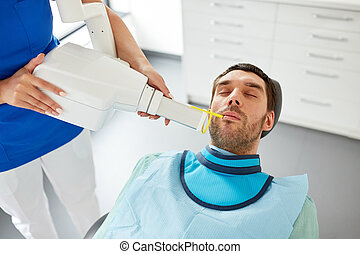 dentist making dental x-ray of patient teeth