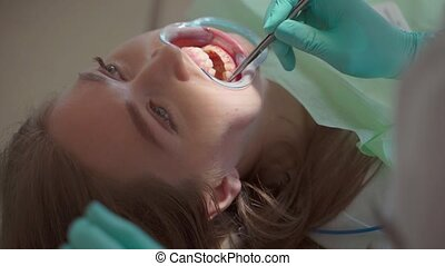 Dentist making professional teeth cleaning female young patient at the dental office. Oral hygiene and prophylactic cleaning.