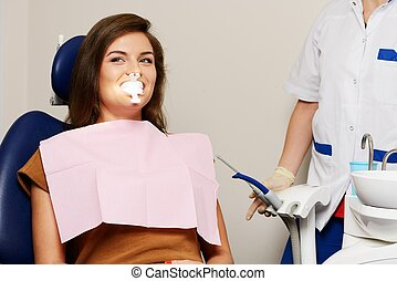 Dentist making teeth whitening procedure to woman patient