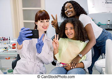 Dentist office, pediatric dentistry. Female pediatric dental specialist making selfie photo on smartphone, together with her patients, little curly mixed raced school girl and her young African mom.