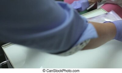 Dentist opens sterilized set of tools for dental checkup