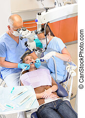 Dentist operating patient through microscope