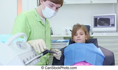 Dentist puts dental tool in girls mouth in surgery