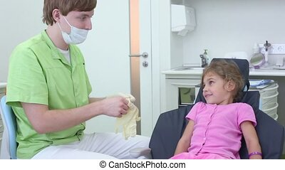 Dentist puts on gloves and girl watch him from dental chair...