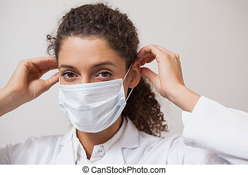 Dentist putting on surgical mask looking at camera at the...