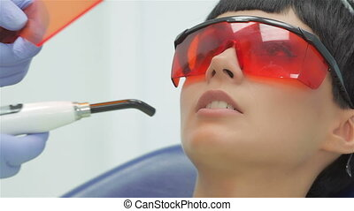 Dentist shines ultraviolet photopolymer seal on fixing it....