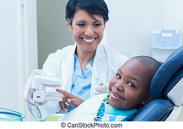 Dentist showing boy prosthesis teeth - Female dentist ...