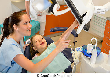 Dentist showing child dental procedure on monitor - Smiling ...