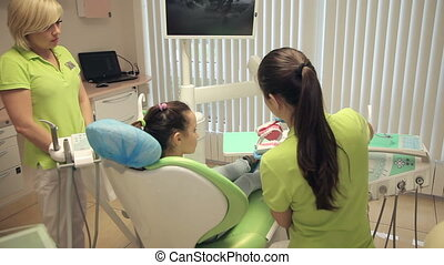 dentist showing girl how correctly to brush teeth