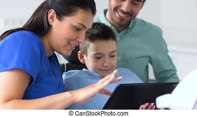 dentist showing tablet pc to kid at dental clinic -...