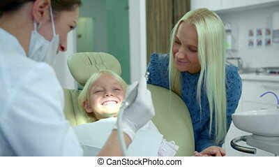 Dentist shows a medical drill, a girl laughs