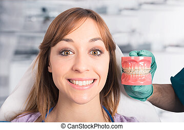 Dentist doctor shows how to apply a brace