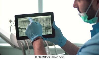 Dentist Shows X-ray on Tablet
