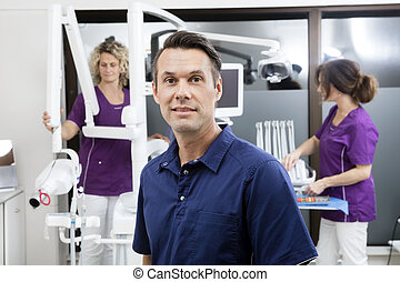 Dentist Smiling While Female Assistants Working At Clinic