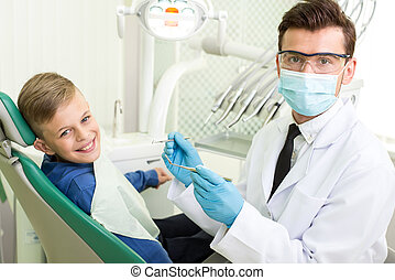 Dentist - Young doctor and the little boy in the dentist's...